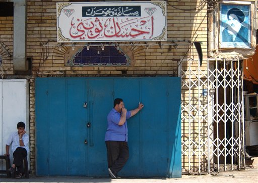 Shop owners stand by their closed establishments after a curfew imposed by a militant group in Baghdad, Iraq