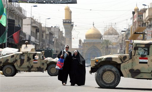 Two Iraqi women walking near military vehicles